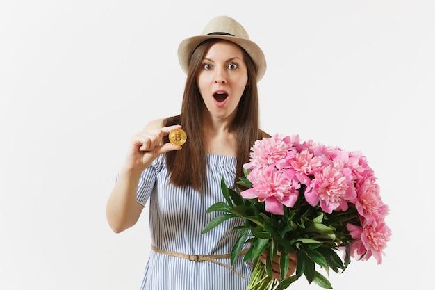 Junge frau im kleid, hut, der bitcoin hält, münze der goldenen farbe, blumenstrauß der schönen rosa pfingstrosenblumen lokalisiert auf weißem hintergrund. geschäft, lieferung, online-shopping, virtuelles währungskonzept.