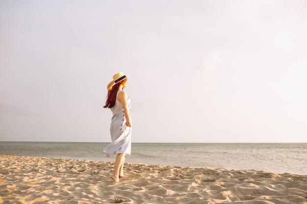 Junge frau im kleid mit strohhut allein am leeren sandstrand bei sonnenuntergang am meer spazieren und lächeln.