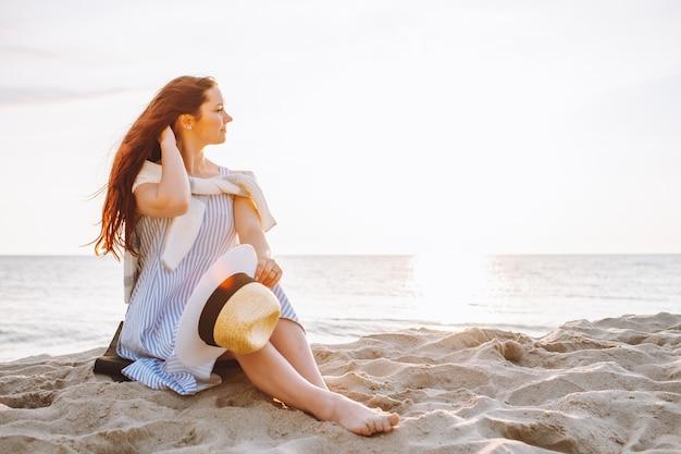 Junge frau im kleid und im strohhut sitzen allein auf leerem sandstrand bei sommersonnenuntergang am seeufer und lächeln. platz für nachricht.