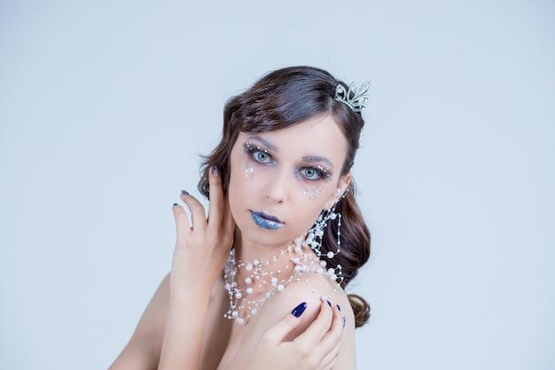 Junge frau im kreativen bild mit silbernem künstlerischem make-up. gesicht der schönen frau.