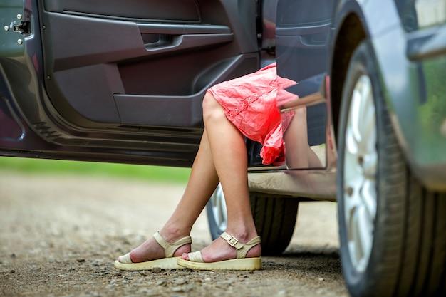 Junge frau im kurzen kleid, das auto mit offener tür auf sonnigem unscharfem landstraßehintergrund hinausgeht.