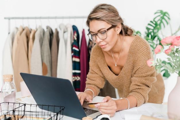 Junge frau im lässigen beigen wollpullover, der laptopanzeige beim bestellen im online-shop betrachtet