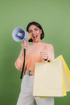 Junge frau im lässigen pfirsichpullover lokalisiert auf grünem olivfarbenem wandschrei im megaphon, der einkaufstaschen hält, kündigt rabatte verkaufsförderung an