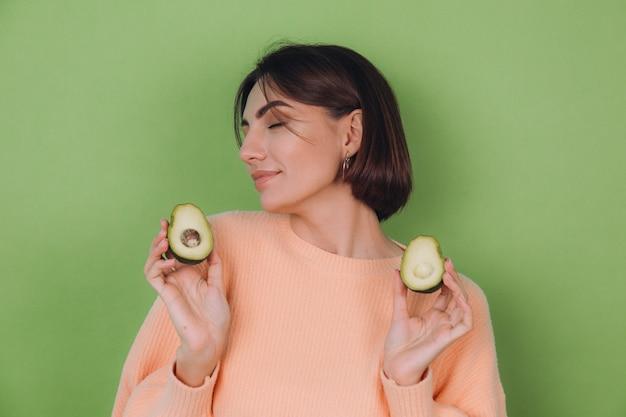 Junge frau im lässigen pfirsichpullover lokalisiert auf grüner olivenwand, die avocado, gesundheits- und hautpflegekonzept, kopienraum hält