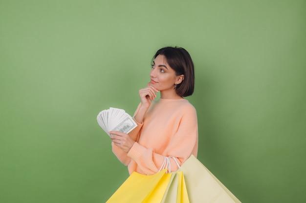 Junge frau im lässigen pfirsichpullover lokalisiert auf grüner olivenwand, die fan von 100-dollar-scheinengeld und einkaufstaschen hält, die positiv lächelnden kopienraum denken