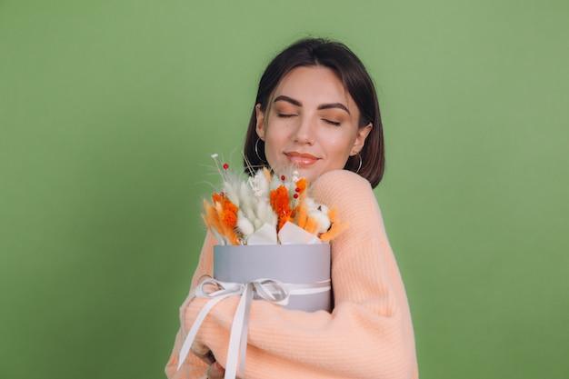 Junge frau im lässigen pfirsichpullover lokalisiert auf grüner olivenwand halten orange weiße blumenkastenzusammensetzung von baumwollblumen gypsophila weizen und lagurus für ein geschenk glücklich erstaunt überrascht
