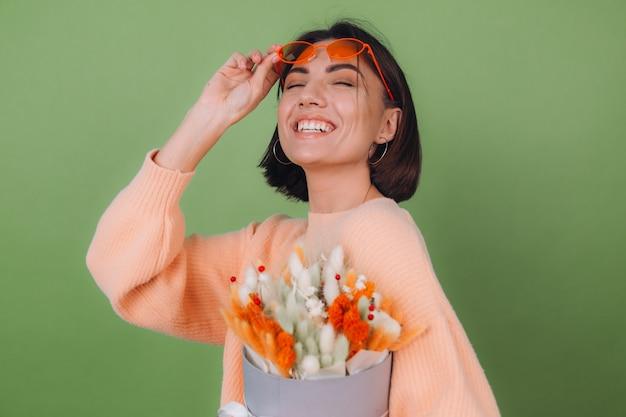 Junge frau im lässigen pfirsichpullover lokalisiert auf grüner olivenwand halten orange weiße blumenkastenzusammensetzung von baumwollblumen, gypsophila, weizen und lagurus für ein geschenk glücklich überrascht