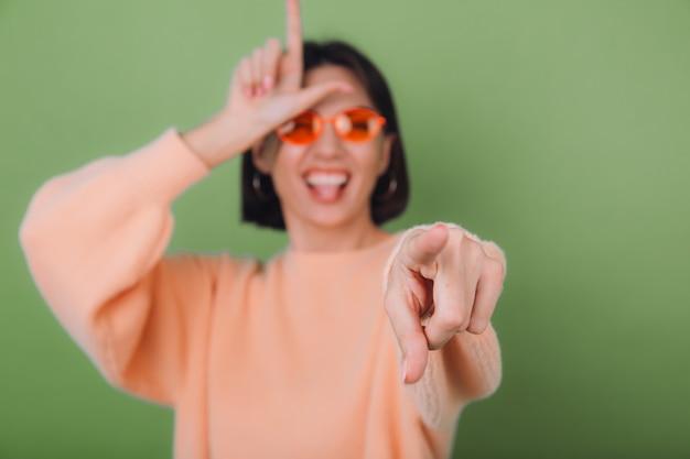 Junge frau im lässigen pfirsichpullover und in den orangefarbenen gläsern lokalisiert auf grüner olivenwand, die auf sie spottnarrentag zeigt, der hornsymbolkopierraum zeigt
