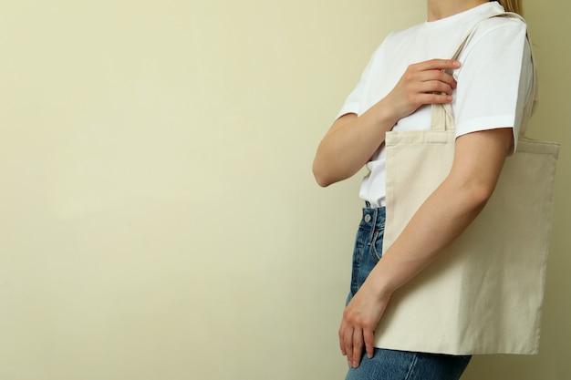 Junge frau im leeren t-shirt mit tasche gegen beigen hintergrund