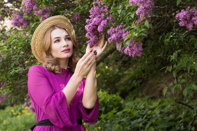 Junge frau im lila kleid posiert in einem garten von flieder