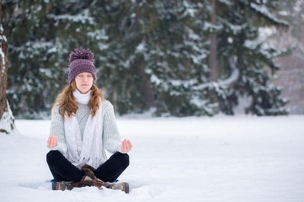 Junge frau im lotussitz im schnee