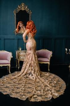 Junge frau im luxuriösen kleid verkleidet sich durch spiegel