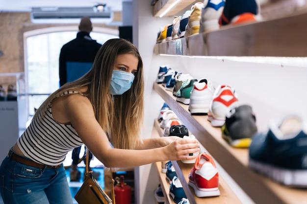 Junge frau im maskeneinkauf an einem bekleidungsgeschäft in der coronavirus-pandemie