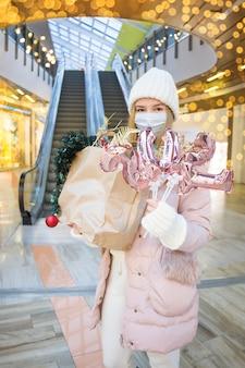 Junge frau im medizinischen maskeneinkauf für weihnachtsgeschenke im einkaufszentrum