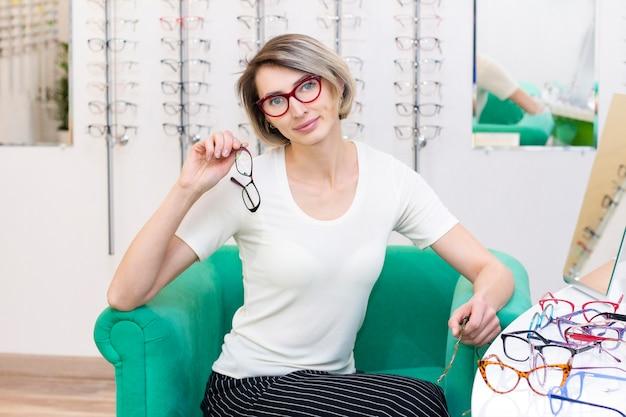 Junge frau im optikgeschäft, die neue brille mit optiker wählt. brille im laden der optik. eine frau wählt eine brille. emotionen. augenheilkunde.