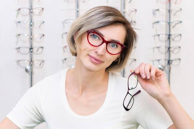 Junge frau im optikgeschäft, die neue brille mit optiker wählt. brillen im laden der optik. eine frau wählt eine brille. emotionen. augenheilkunde.