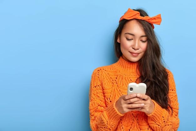 Junge frau im orangefarbenen pullover, der auf ihrem smartphone plaudert