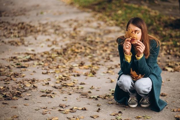Junge frau im park, die augen mit herbstlaub schließt