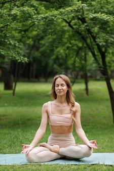 Junge frau im park im sommer beschäftigt sich mit yoga und meditation