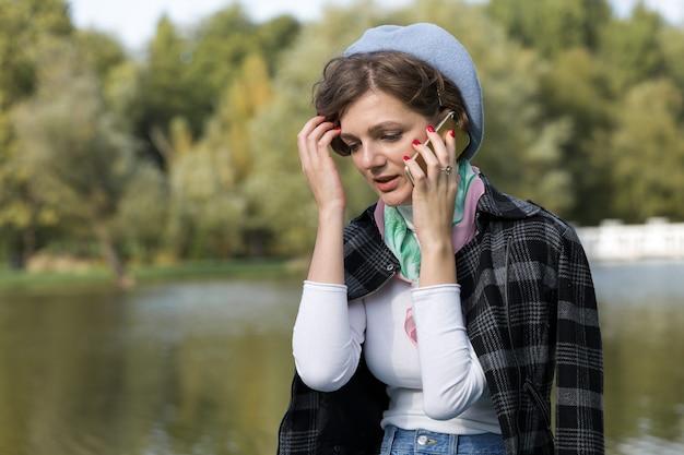 Junge frau im park spricht mit dem handy. nettes mädchenporträt im französischen stil.