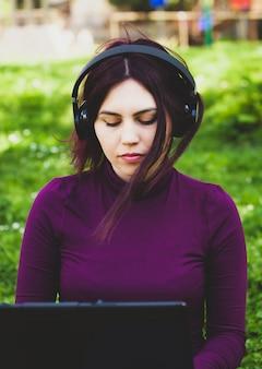 Junge frau im park unter verwendung der hörenden musik der laptop-computers.