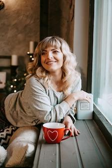 Junge frau im plaid mit tasse heißem tee in einem gemütlichen weihnachtsinnenraum. das konzept der vorbereitung auf die feiertage, machen sie einen wunsch und träumen sie