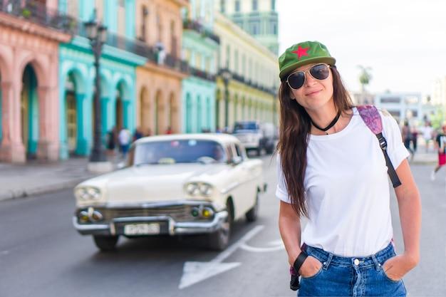 Junge frau im populären bereich in altem havana, kuba. schöner mädchenreisender, bunte häuser in der stadt