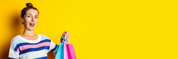 Junge frau im pullover, der einkaufstaschen auf gelbem hintergrund hält.