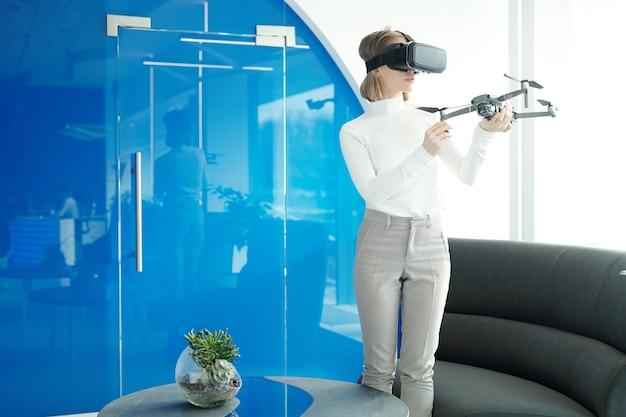 Junge frau im pullover, der in der modernen lobby steht und drohne mit virtual-reality-gerät bedient