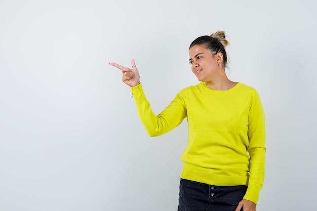 Junge frau im pullover, jeansrock, der zur seite zeigt und selig aussieht