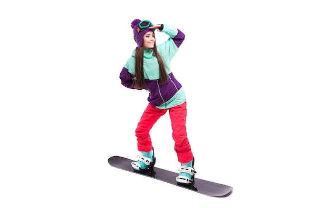 Junge frau im purpurroten skikostüm-fahrsnowboard