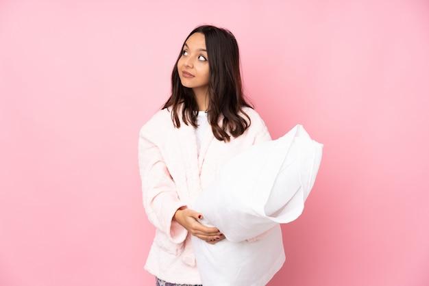 Junge frau im pyjama auf rosa, das zweifel macht, die seite suchen