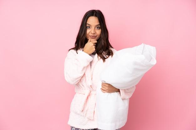 Junge frau im pyjama auf rosa wand denken