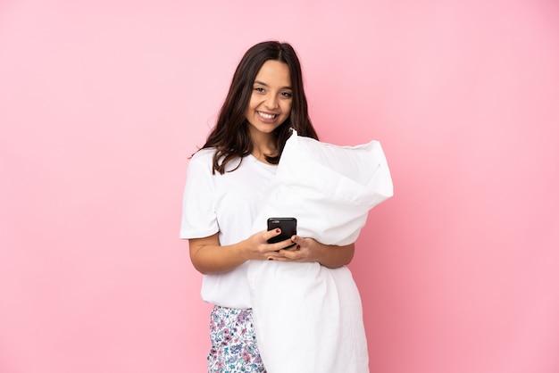 Junge frau im pyjama auf rosa wand, die eine nachricht mit dem handy sendet