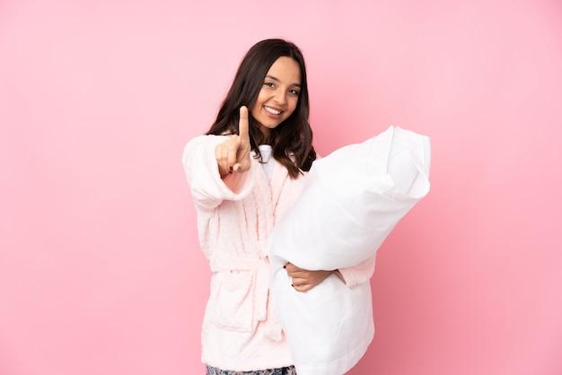 Junge frau im pyjama auf rosa wand, die einen finger zeigt und hebt