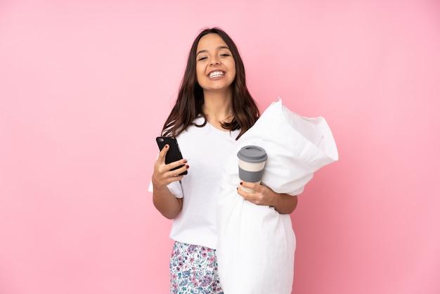 Junge frau im pyjama auf rosa wand, die kaffee hält, zum wegnehmen und ein handy