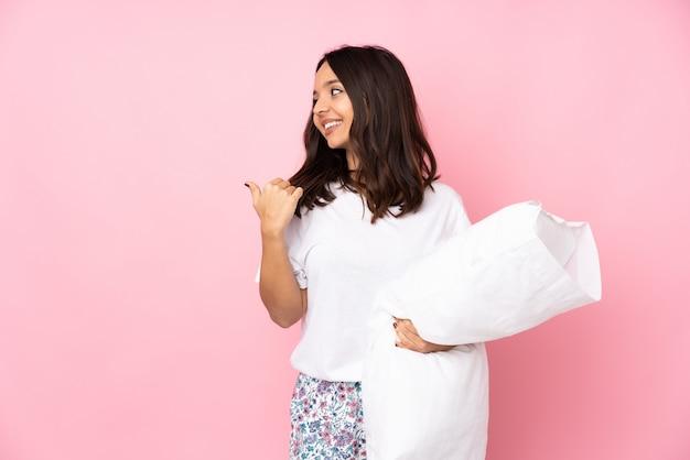 Junge frau im pyjama auf rosa wand, die zur seite zeigt, um ein produkt zu präsentieren