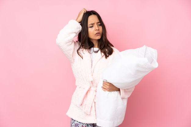 Junge frau im pyjama auf rosa wand, die zweifel beim kratzen des kopfes hat