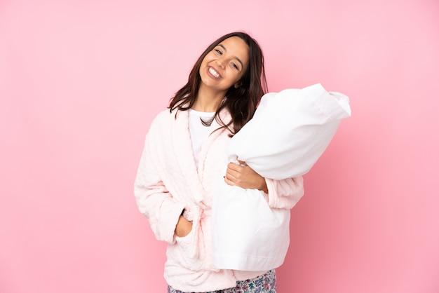Junge frau im pyjama auf rosa wand lachend