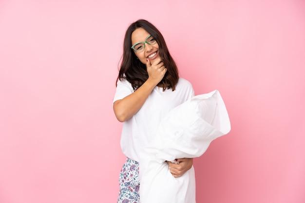 Junge frau im pyjama auf rosa wand mit brille und lächelnd