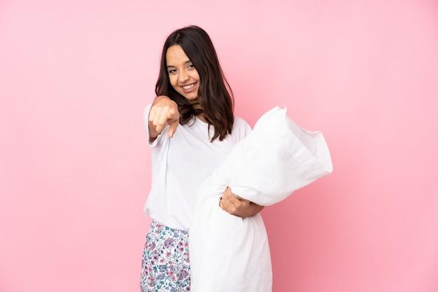 Junge frau im pyjama auf rosa wand zeigt finger auf sie mit einem selbstbewussten ausdruck