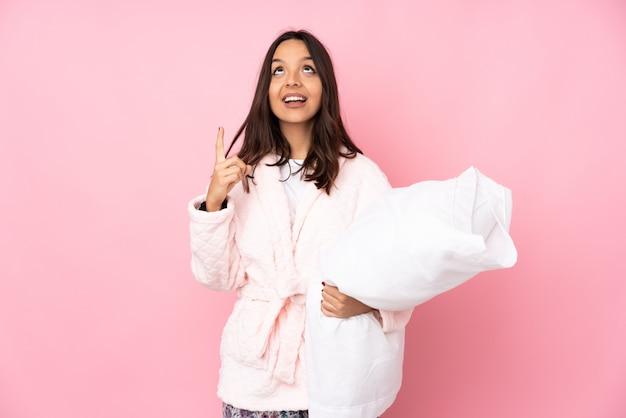Junge frau im pyjama auf rosa wand zeigt nach oben und überrascht