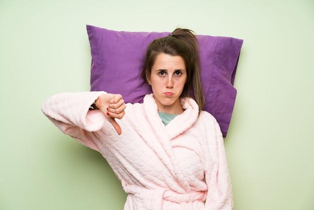 Junge frau im pyjama, der schlechtes signal macht