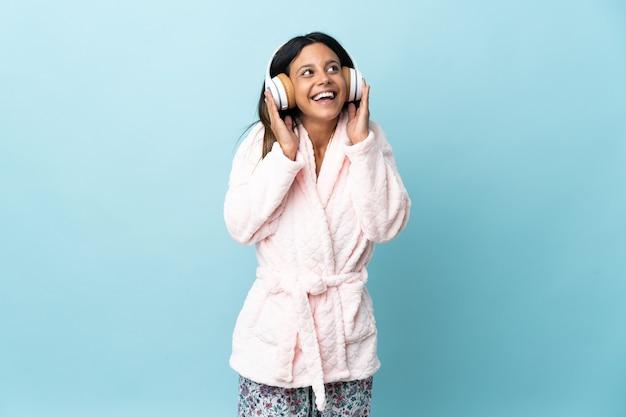 Junge frau im pyjama im pyjama und hält ein kissen und hört musik