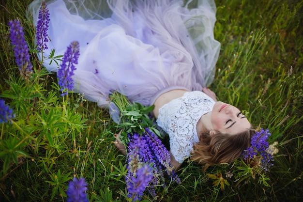 Junge frau im reichen kleid liegt mit blumenstrauß von violetten blumen auf grünem feld