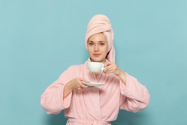 Junge frau im rosa bademantel nach dem duschen, das kaffee lächelt, der auf blau lächelt