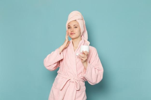 Junge frau im rosa bademantel nach dem duschen mit creme auf blau
