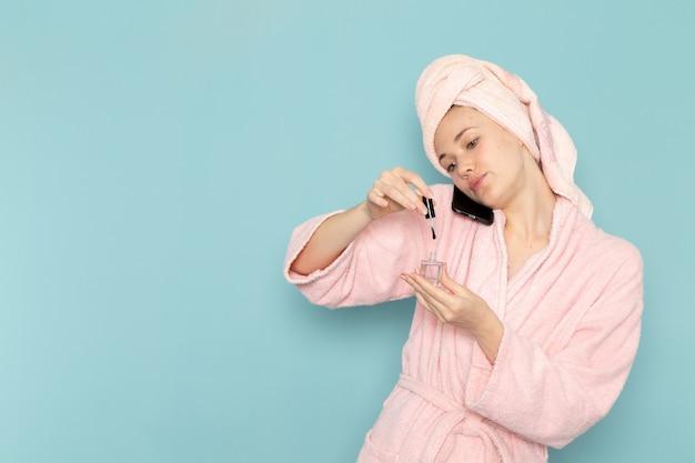 Junge frau im rosa bademantel nach der dusche, die am telefon spricht und ihre nägel auf blau malt