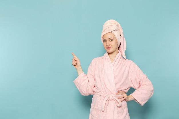 Junge frau im rosa bademantel nach der dusche, die gerade mit lächeln auf blau aufwirft