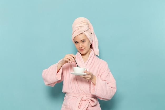Junge frau im rosa bademantel nach der dusche, die kaffee auf blau mischt